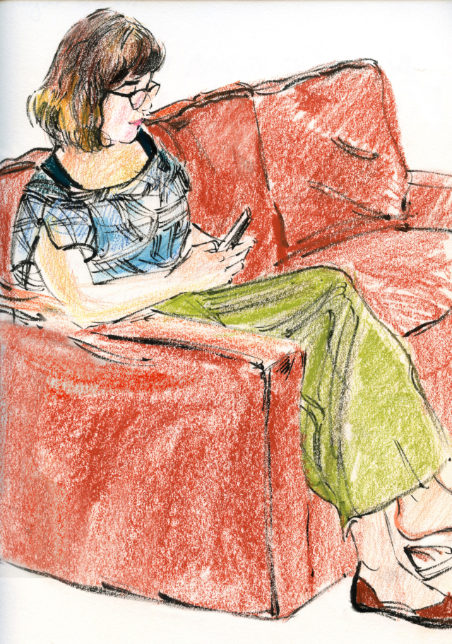 Kate reading on red sofa